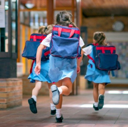 Three girl students running towards their rooms